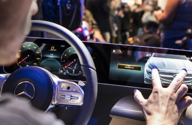 A man puts two fingers on his MBUX touch screen in the cabin of his Mercedes-Benz vehicle.