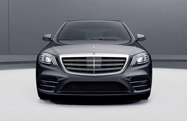 Black Mercedes-Benz S-450 sedan, a member of the S-Class, sits in a futuristic garage.