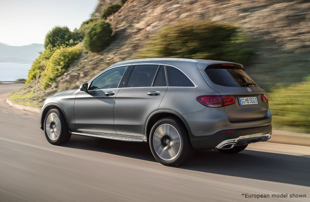 2020 Mercedes-Benz GLC drives around a scenic highway bend by some green plants.