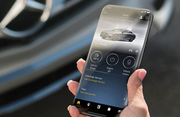 Hand holds a smartphone with Mercedes app on it